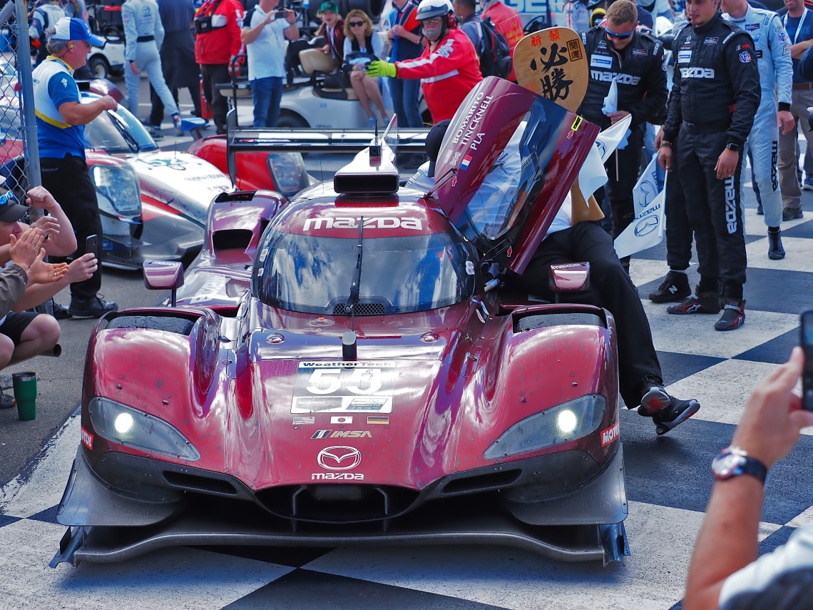 Mazda #55 enters the victory podium with an extra passenger.